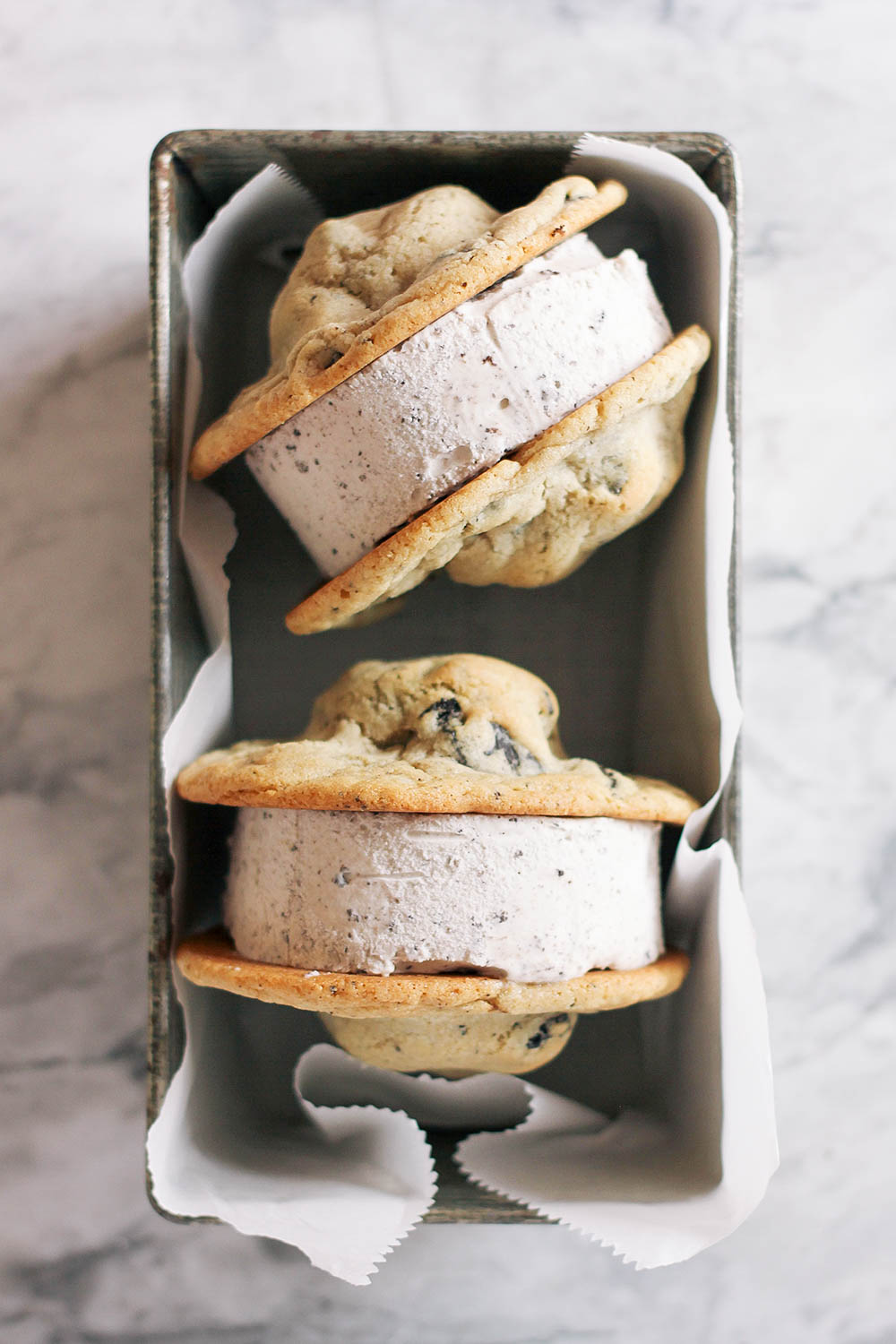 Triple Oreo ice cream sandwiches with Oreos baked right into the cookies. Get the full recipe at HomemadeBanana.com #recipe #oreo #dessert #icecreamsandwich